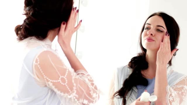 tägliche-Creme-Natur-Anwendung-für-gesund-aussehende-Haut-Frau-mit-makellose-Haut-in-Spiegel
