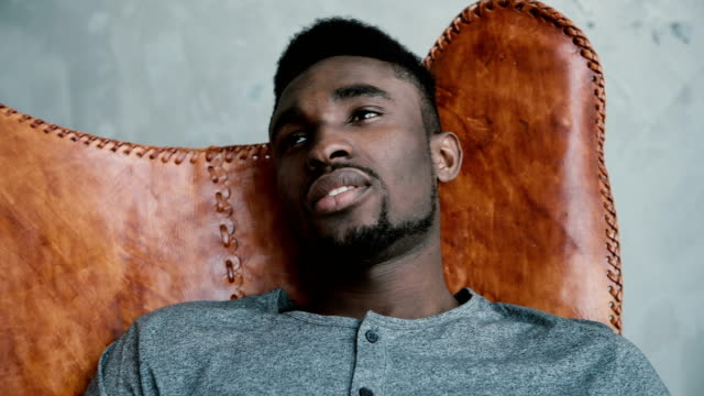 Portrait-of-young-African-male-sitting-in-leather-chair-thinking-about-something-and-smiling-Man-looks-thoughtfully