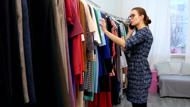 Cute-young-woman-talking-on-her-cell-phone-while-checking-out-some-clothes-at-the-store