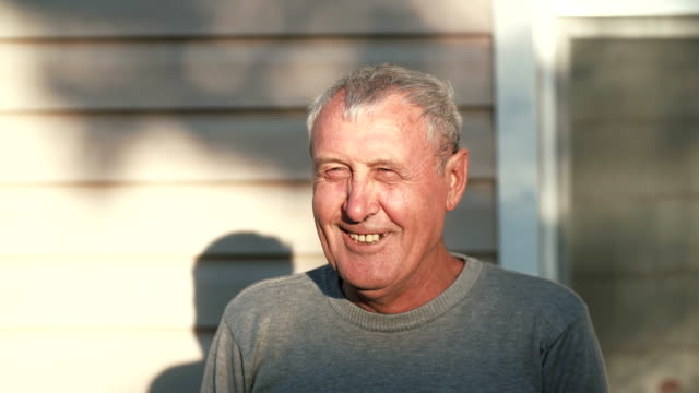 Close-up-of-smiling-old-man-face-standing-in-front-of-camera-smiling-laughing-talking-outdoor-in-sunlight-4K
