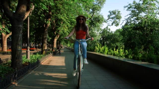 joven-hermosa-mujer-montando-una-bicicleta-en-un-parque