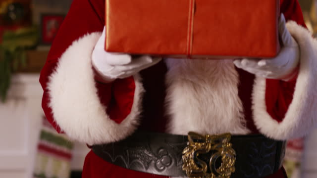 Santa-Claus-peeks-out-from-behind-stack-of-gifts