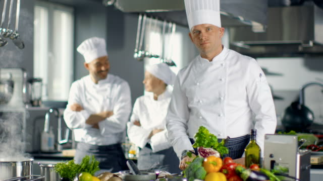 Famous-Chef-of-a-Big-Restaurant-Prepares-Dishes-and-Smiles-On-Camera-In-the-Background-Two-Apprentices-and-Modern-Kitchen-