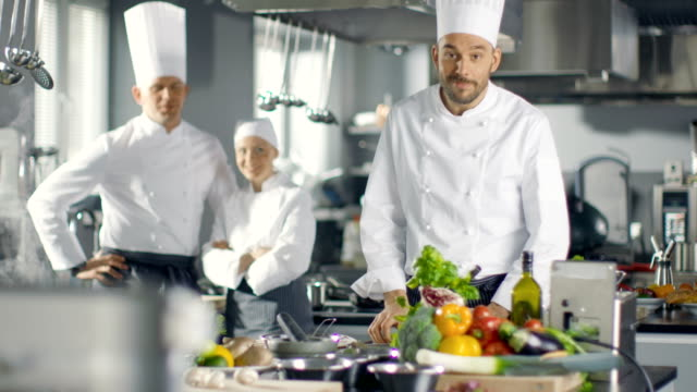 Famous-Chef-of-a-Big-Restaurant-Crosses-Arms-and-Smiles-in-a-Modern-Kitchen-His-Staff-in-Smiling-in-the-Background-