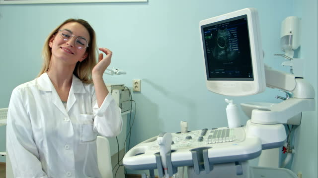 Smiling-female-doctor-in-glasses-looking-into-the-camera-in-ultrasound-room