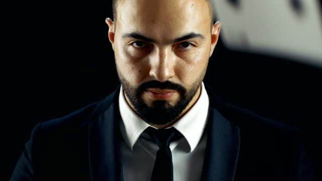 Close-up-retrato-de-un-hombre-con-barba-mirando-a-la-cámara-y-tarjetas-de-juegos-de-azar-lloviendo-sobre-él-en-cámara-lenta-