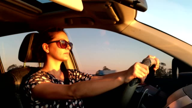 Drive-Goal-oriented-woman-in-her-30-s-driving-during-golden-hour