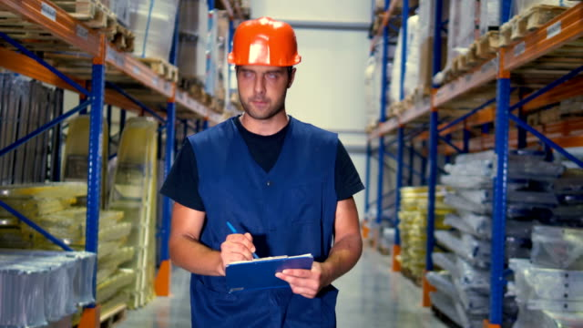 A-warehouse-supervisor-takes-notes-on-his-clipboard-