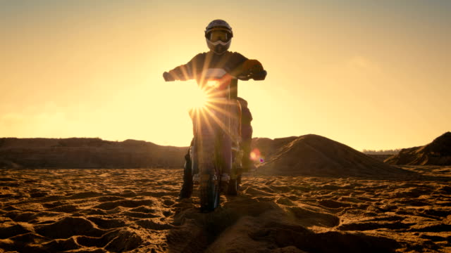 Low-Angle-Shot-of-the-Professional-Motocross-Driver-Sitting-on-His-FMX-Motorcycle-Twisting-Full-Throttle-Handle-and-Starting-to-Ride-This-Extreme-Off-Road-Terrain-Track