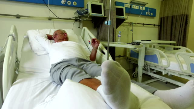 Elderly-70-plus-year-old-man-recovering-from-surgery-in-a-hospital-bed