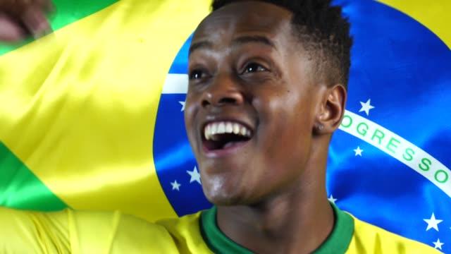 Joven-brasileño-negro-a-hombre-celebrando-con-la-bandera-de-Brasil