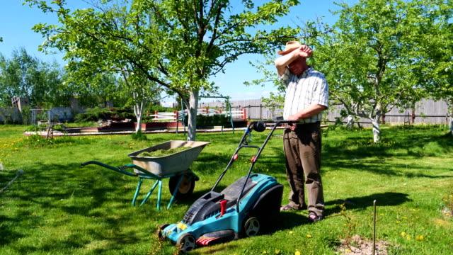 Un-hombre-está-de-pie-con-un-cortacésped-en-un-hermoso-jardín-