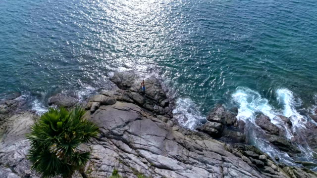 Aerial:-Two-partners-doing-Acro-Yoga-on-the-rocks-near-the-sea-