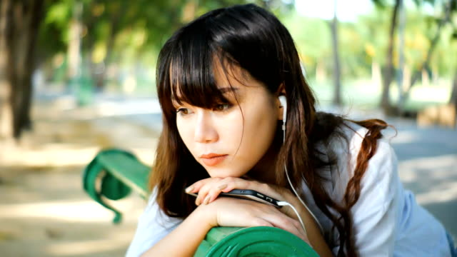 Beautiful-young-hipster-sad-asian-woman-emotionally-listening-music-in-headphones-with-smartphone-sitting-on-the-park-bench-in-summer-sunset-sun-light-