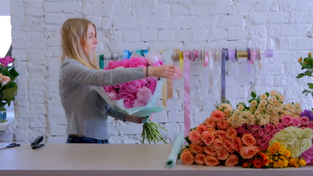 Florist-wraps-flowers-in-gift-paper-at-flower-shop