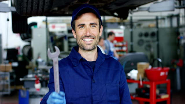 Portrait-of-a-young-beautiful-car-mechanic-in-a-car-workshop-in-the-background-of-service-Concept:-repair-of-machines-fault-diagnosis-repair-specialist-technical-maintenance-and-on-board-computer