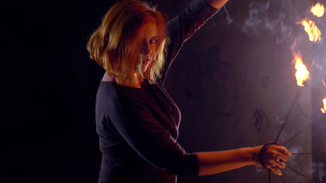Yong-woman-artist-performing-fire-show-at-dark-in-slow-motion-