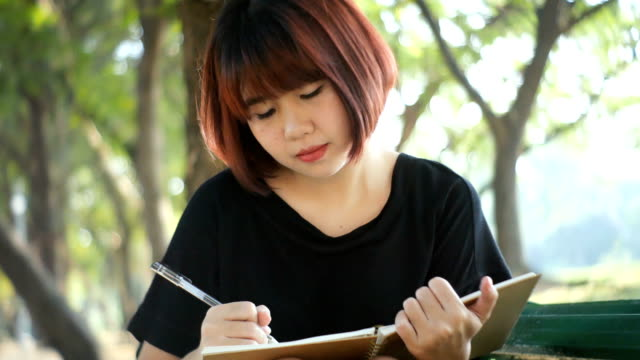 Happy-hipster-young-asian-woman-writing-into-her-diary-in-park-Happy-hipster-young-asian-woman-working-on-notebook-in-park-Student-studying-outdoors-Lifestyle-woman-outdoor-concept-