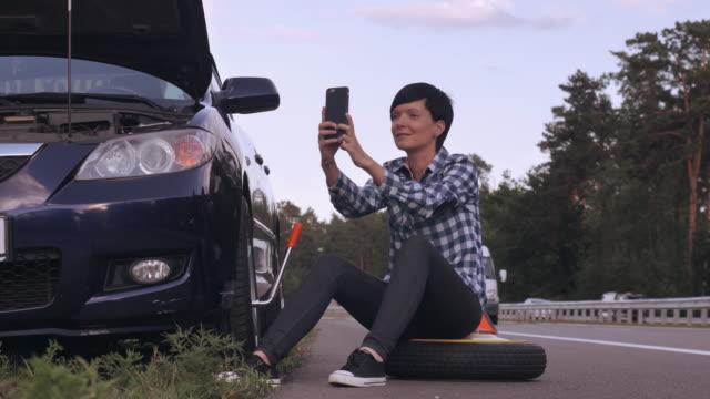 Mujer-caucásica-intentar-cambiar-un-neumático-al-aire-libre-
