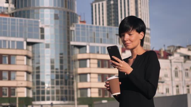 Cheerful-girl-enjoy-coffee-use-smartphone-outdoors-