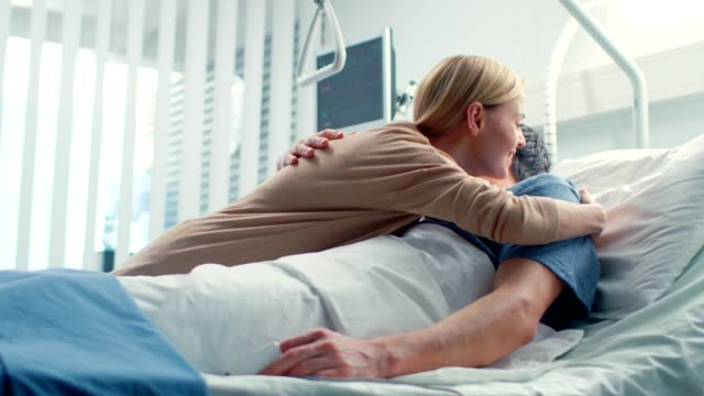 In-the-Hospital-Happy-Wife-Visits-Her-Recovering-Husband-who-is-Lying-on-the-Bed-They-Lovingly-Embrace-and-Smile-