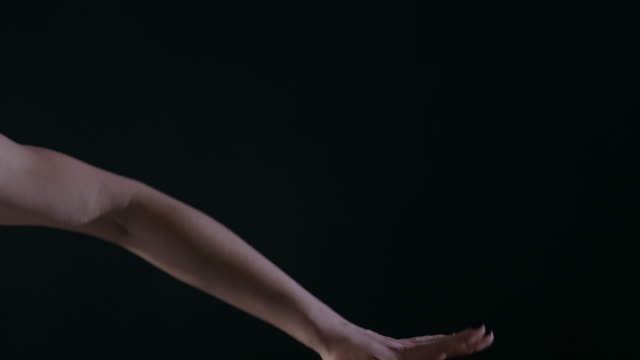 Ballerina-dancing-on-stage-or-dark-classroom-studio-close-up-of-only-hands-with-magic-light-on-background-4k