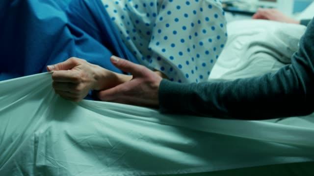 En-la-mujer-del-Hospital-en-trabajo-empuja-a-dar-a-luz-el-tensar-el-momento-me-agarra-hojas-de-dolor-Primer-plano-de-la-cara-obstetras-ayudar-marido-soporta-