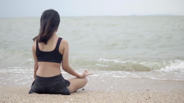 Joven-de-asia-practicando-yoga-en-el-beach-4K-resolución