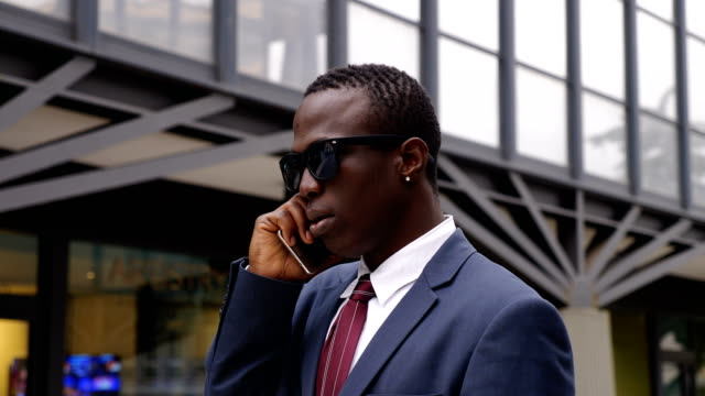 Busy-confident-black-african-manager-talking-by-phone-in-the-street