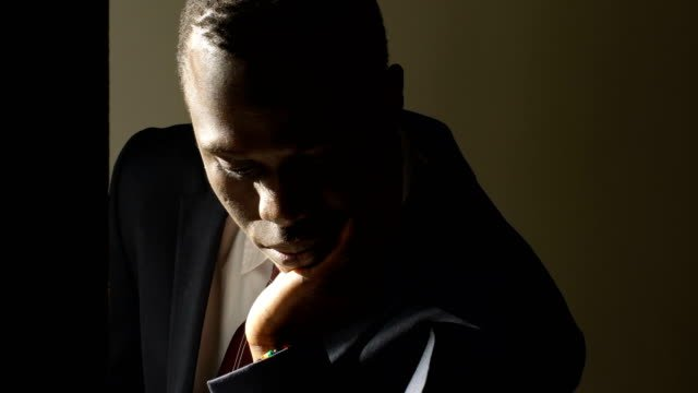 Thoughtful-worried-young-black-business-man-in-the-dark