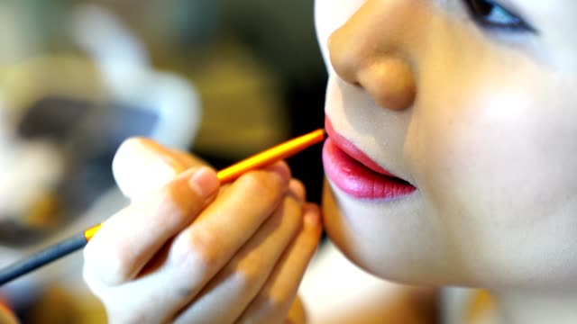 Close-up-woman-is-makeup-applying-lipstick-on-your-mouth-