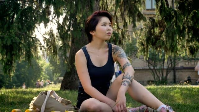 Moda-hipster-mujer-asiática-joven-con-tatuaje-sentado-sobre-la-hierba-en-el-parque-cerca-de-la-Universidad-pensativo