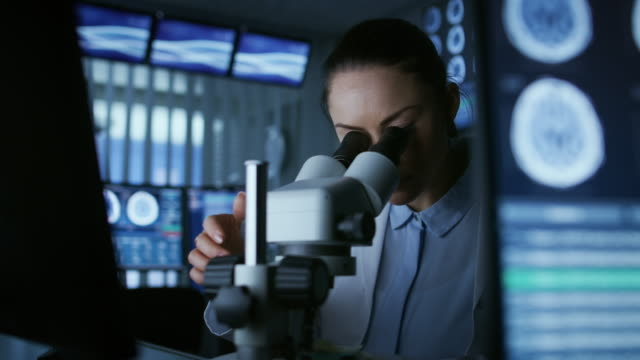 Female-Medical-Research-Scientist-Looking-Through-the-Microscope-Types-Acquired-Data-in-the-Computer-Laboratory-In-the-Laboratory-with-Multiple-Screens-Showing-MRI-/-CT-Brain-Scan-Images-