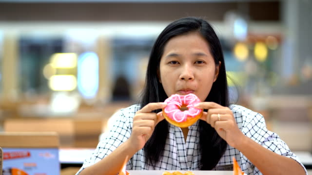 Asian-women-are-eating-donuts-happily-