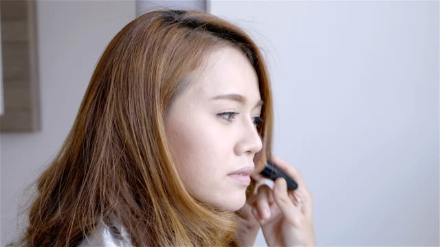 Beautiful-asian-woman-make-up-in-front-of-a-mirror-at-home-in-the-morning-bedroom-Beauty-Concept