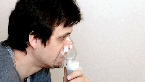 Use-nebulizer-and-inhaler-for-the-treatment-Young-man-inhaling-through-inhaler-mask-and-coughs-Side-view-