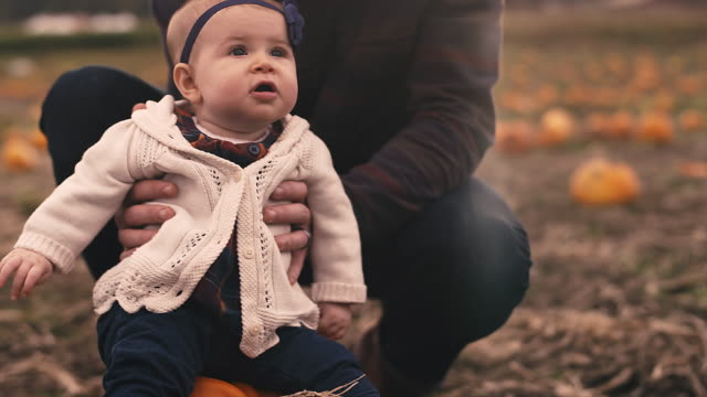 Close-up-of-a-baby-sitting-on-a-pumpkin-at-a-pumpkin-patch-with-her-dad-holding-her-up