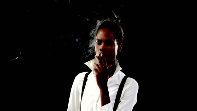 Androgynous-woman-smoking-cigar-against-black-background