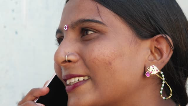 Young-lady-with-beautiful-face-on-mobile-phone-cellphone-handy-smart-contact-notification-types-message-talks-speaks-communication-device-wireless-network-signal-smile-laughs-close-up-in-Rajasthan