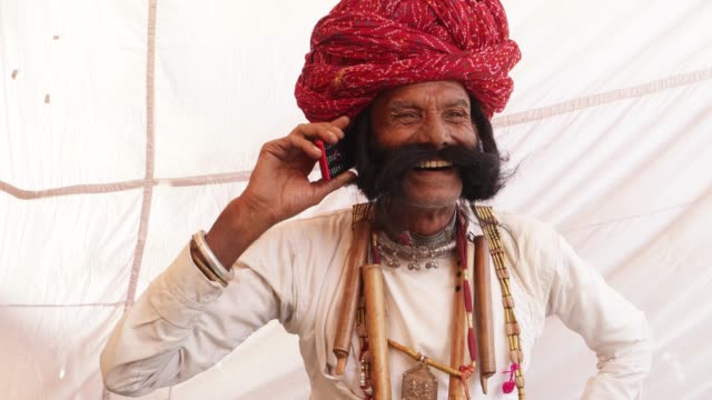 Hand-held-Rajasthani-elderly-male-on-a-smart-cell-phone-mobile-conversation