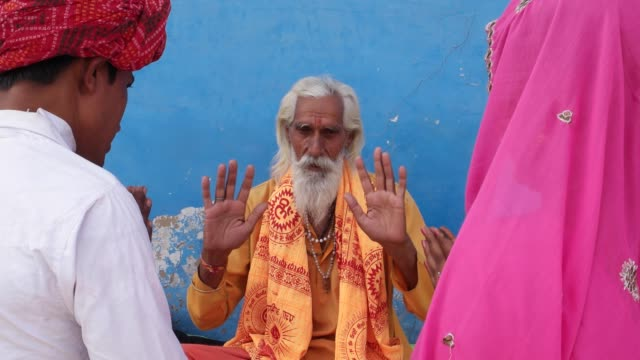 Indian-holy-man-Sadhu-hands-raised-and-blessing-a-couple-with-folded-hands-in-Pushkar-Rajasthan-husband-wife-bride