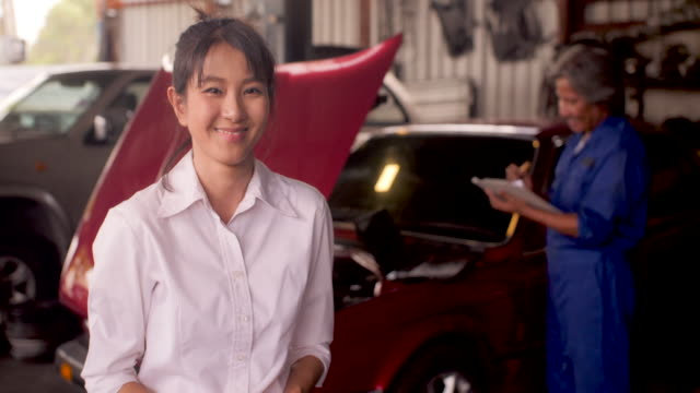 Portrait-of-smiling-customer-while-a-mechanic-works-on-a-car-in-the-background-car-service-concept-dolly-shot