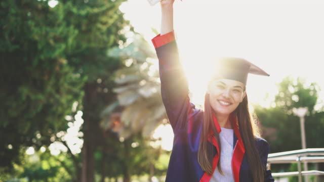 Graduated-student-raising-her-diploma-up