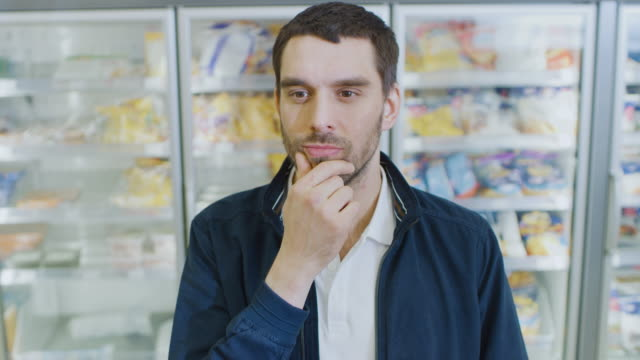 Portrait-Shot-of-the-Handsome-Man-Thinking-Very-Hard-and-Choosing-Tin-Can-from-the-Canned-Goods-Section-Plaves-it-i-His-Shopping-Cart-In-the-Background-Frozen-Goods-Section-of-the-Store-