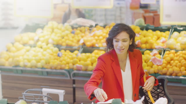 At-the-Supermarket:-Portrait-of-the-Beautiful-Smiling-Woman-Choosing-Organic-Fruits-In-the-Fresh-Produce-Aisle-and-Puts-them-into-Shopping-Basket-High-Angle-Shot-
