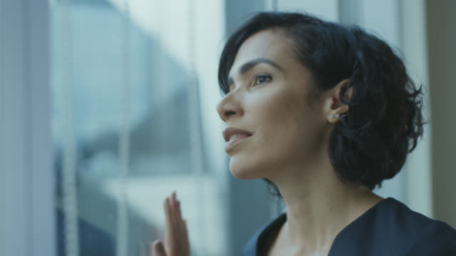 Close-up-Portrait-of-the-Beautiful-Young-Businesswoman-Looking-Thoughtfully-out-of-Her-Office-Window-Confident-and-Attractive-Hispanic-Woman-Thinking-about-Her-Business-Project-