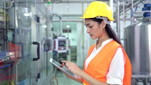 Mujer-ingeniero-industrial-en-el-trabajo-en-la-fábrica-Hermosa-joven-ingeniero-chino-trabajando-en-fábrica-grande-Con-casco-y-chaqueta-Máquina-automática-de-alta-tecnología-en-segundo-plano-