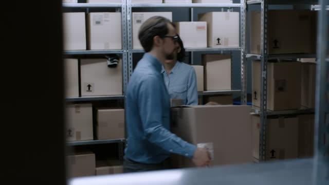 Trabajador-de-almacén-femenino-pone-caja-de-cartón-de-un-estante-y-sonrisa-encantadora-En-las-filas-del-fondo-de-estantes-llenos-de-cajas-de-cartón-y-paquetes-llenan-de-productos-listos-para-el-envío-