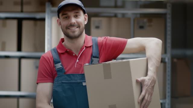 Retrato-de-almacén-guapo-trabajador-uniforme-tiene-sonrisas-y-paquete-de-la-caja-de-cartón-