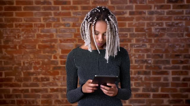 Young-African-girl-with-dreadlocks-using-a-tablet-computer-typing-Brick-wall-in-the-background-